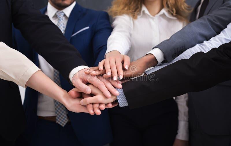 Eniga händer av affären team på arbetsplatsbakgrund royaltyfri foto