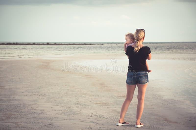 Enige moeder met baby die op haar handen de afstand onderzoeken bij horizon over overzees bij strand met exemplaarruimte royalty-vrije stock afbeelding