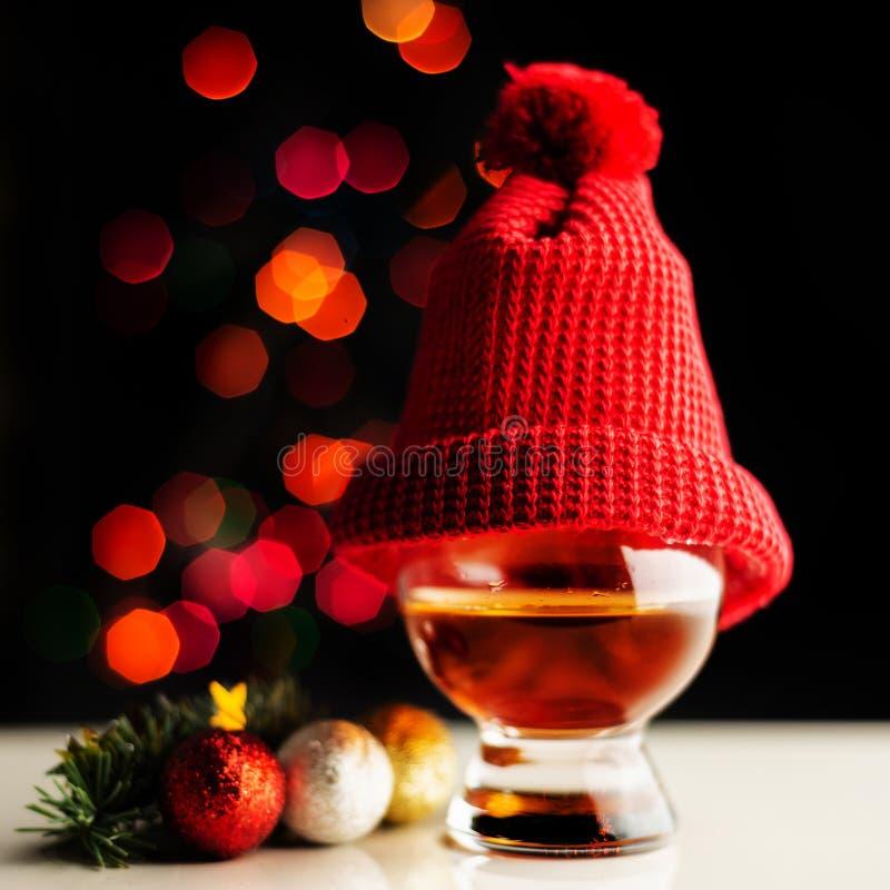 Enige moutwisky in het proeven van glas op mede Kerstmisachtergrond, stock foto's