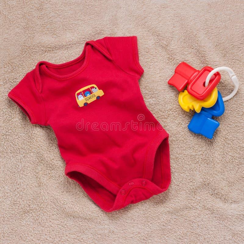 Enige rode babybodysuit met plastic stuk speelgoed sleutels royalty-vrije stock foto