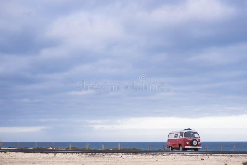 Enige rode oude uitstekende die bestelwagen dichtbij de oceaan wordt geparkeerd vakantie trave stock afbeelding