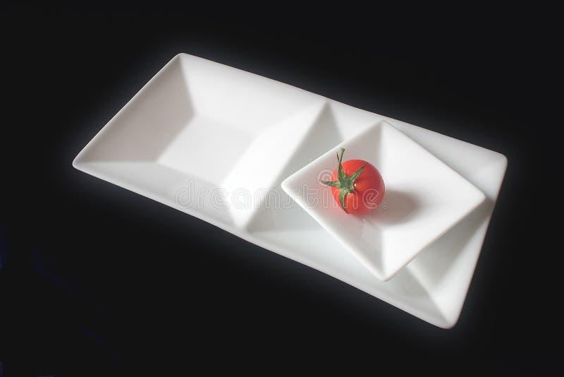 Download Enige Tomaat Op Geregelde Schotels Stock Afbeelding - Afbeelding bestaande uit recept, dieet: 34075