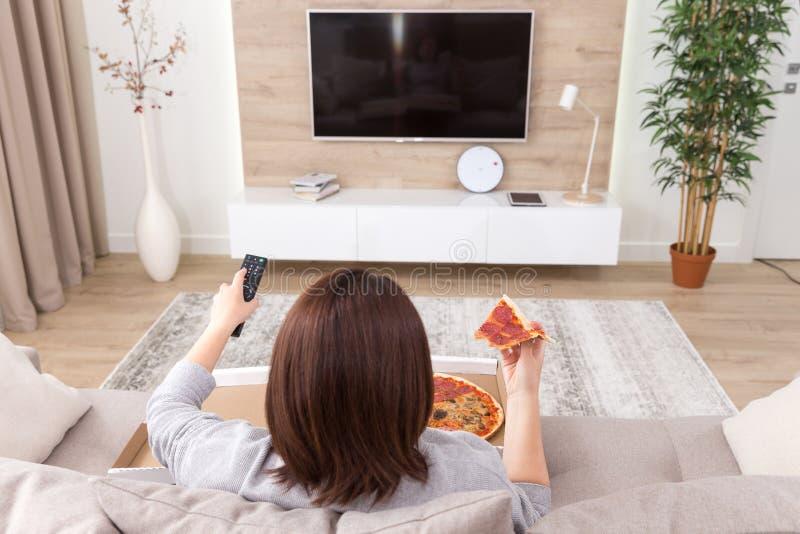 Enige vrouw die pizza eten en op TV letten stock fotografie