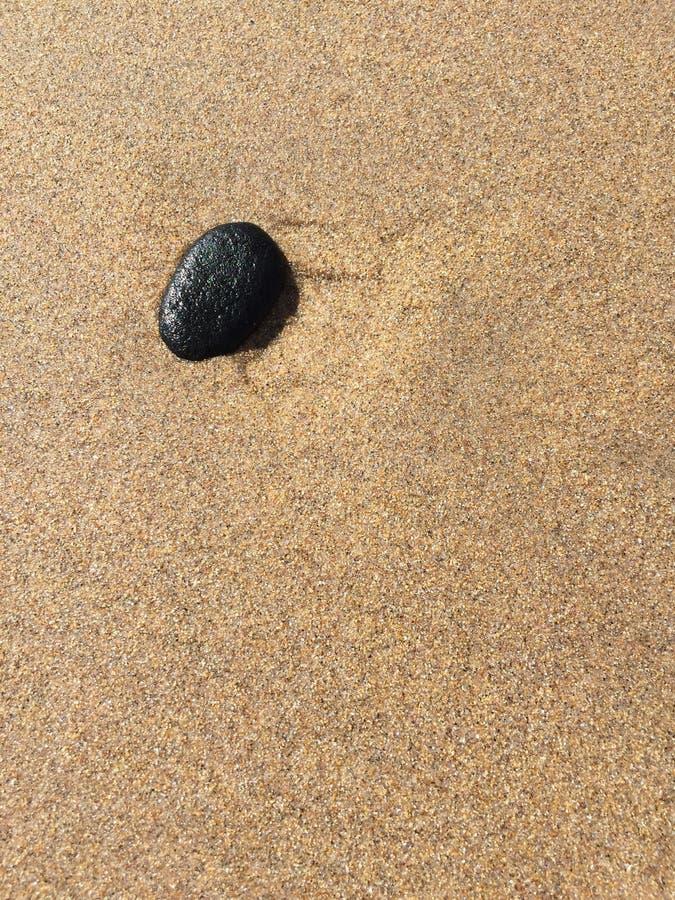 Enige zwarte kiezelsteen op zand stock foto