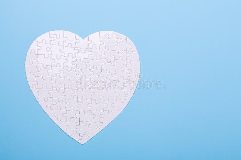 Enigma branco na forma do coração no tratamento azul do conceito da serra de vaivém do fundo de comprimidos da doença cardíaca fotos de stock royalty free