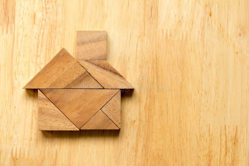 Enigma do Tangram na forma home no fundo de madeira fotografia de stock royalty free
