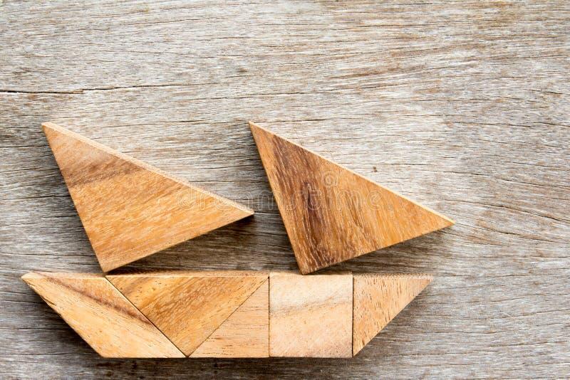 Enigma do Tangram no barco de navigação no fundo de madeira imagem de stock