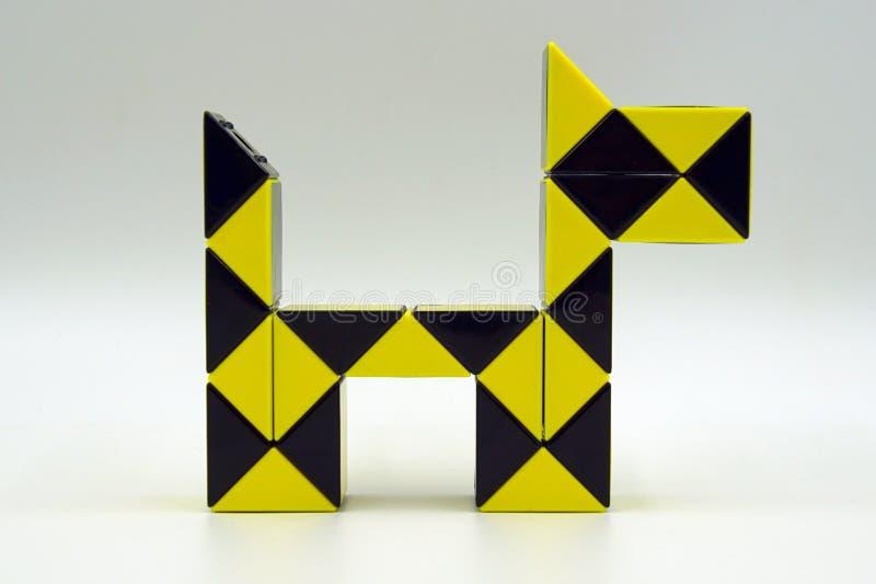 Enigma mágico da torção amarela da serpente do ` s de Rubik - cão imagens de stock royalty free