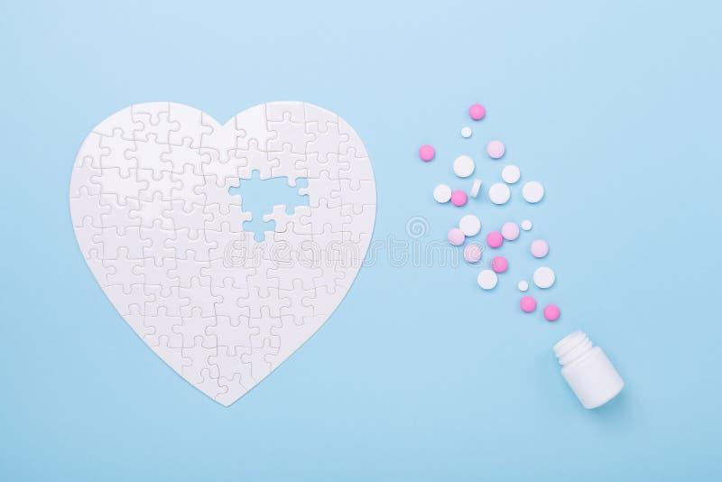 Enigma na forma dos comprimidos brancos e cor-de-rosa do coração no tratamento azul do conceito da serra de vaivém do fundo de co fotografia de stock