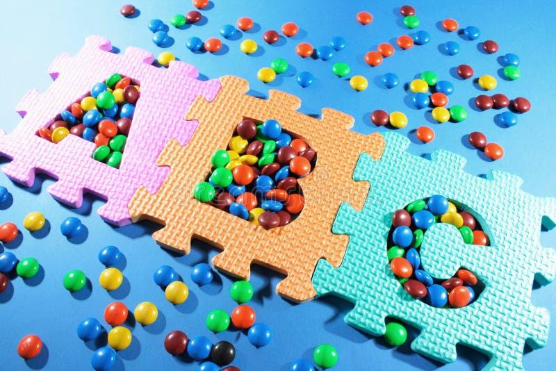 Enigmas do alfabeto e Lollies do chocolate imagens de stock