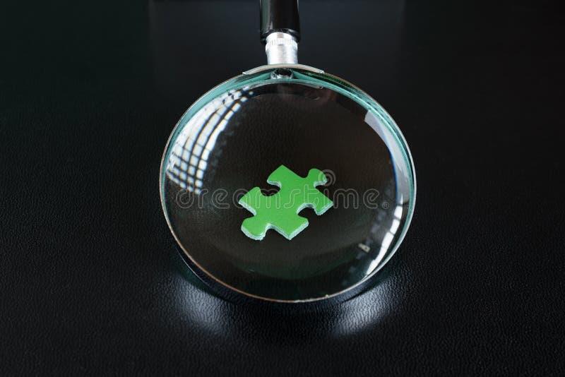 Enigmas verdes e lupa imagem de stock