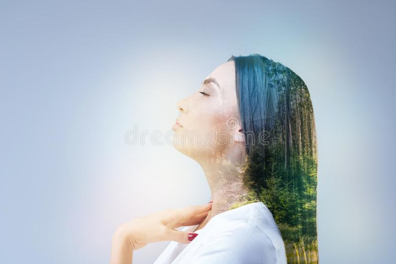 Enigmatical female person thinking about nature. Relax time. Cheerful girl keeping eyes closed and putting hand on her neck while standing in semi position royalty free stock photos