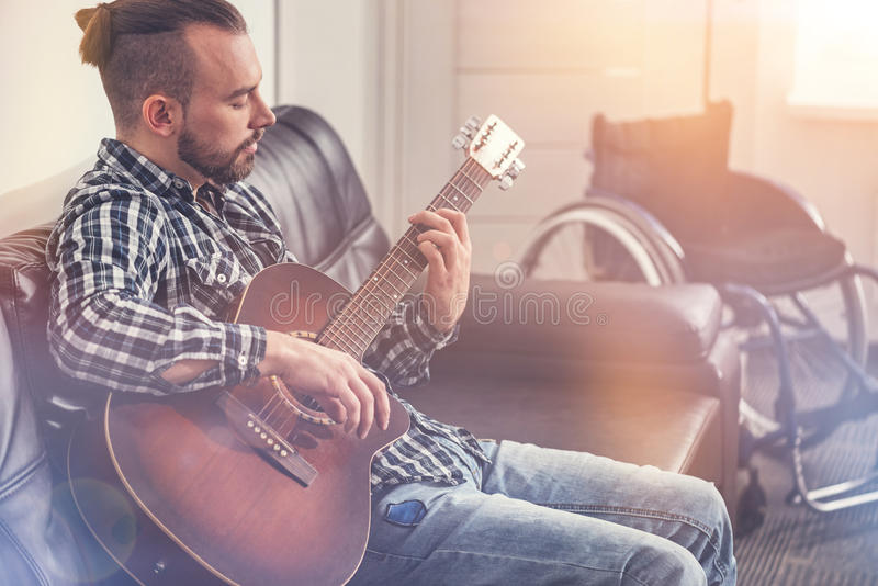 Enigmatical young man playing the guitar stock photos