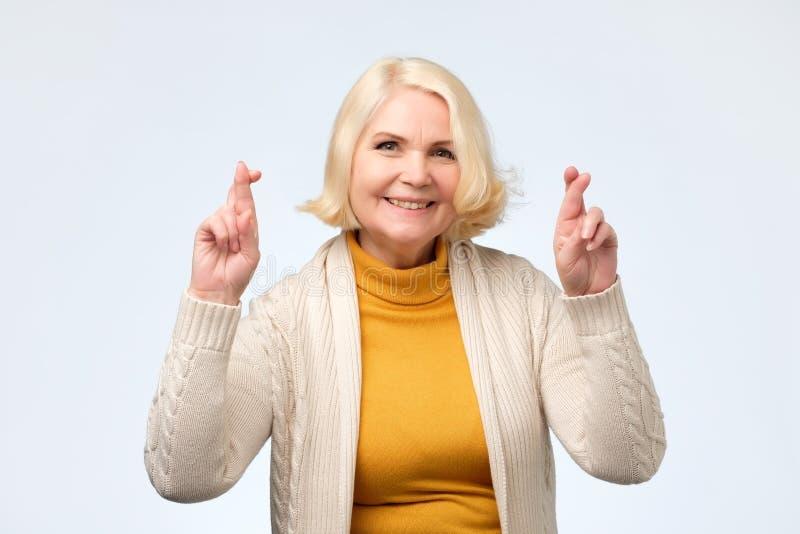 Enior Kaukasische vrouw die kruisend vingers met hoop en gesloten ogen glimlachen stock foto