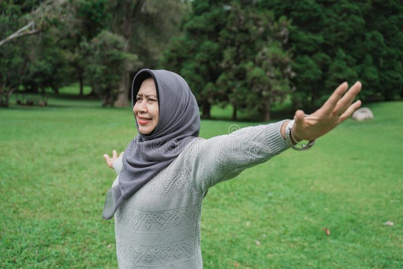 Enior muslim woman relaxing taking deep breath and stretching. Happy senior muslim woman relaxing taking deep breath and stretching and exercising outdoor in the royalty free stock image