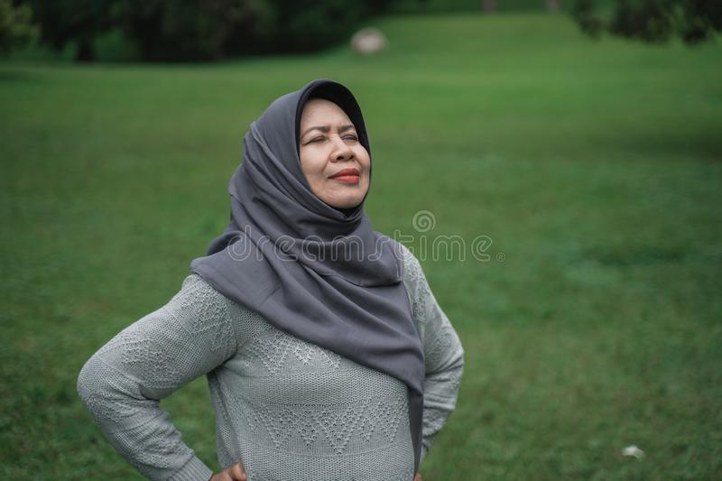 Enior muslim woman relaxing taking deep breath and stretching. Happy senior muslim woman relaxing taking deep breath and stretching and exercising outdoor in the royalty free stock photos