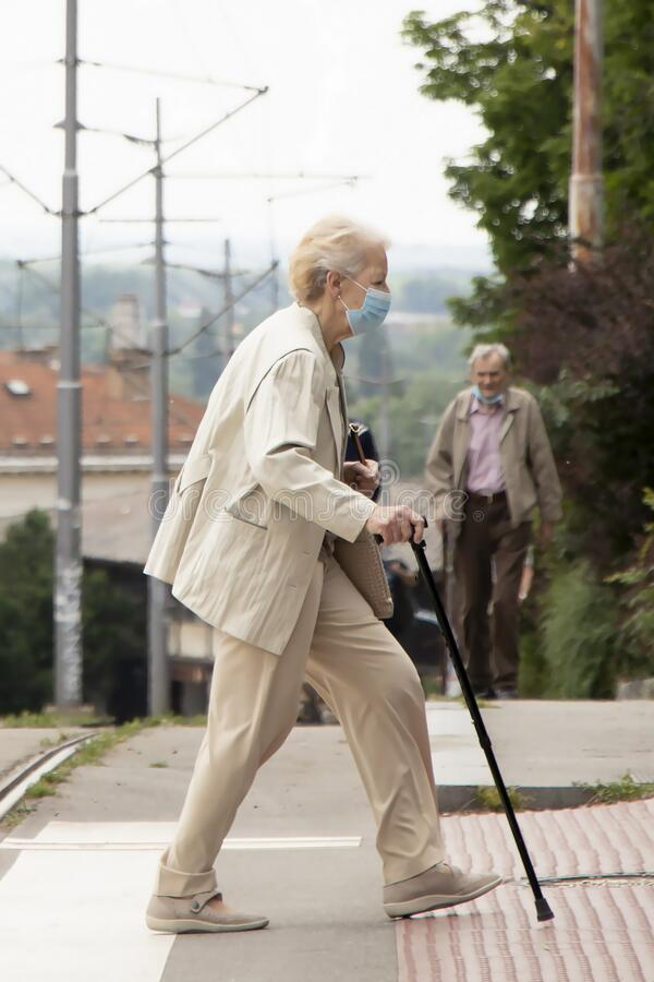 Enior woman wearing face surgical mask walking with a cane stock photo