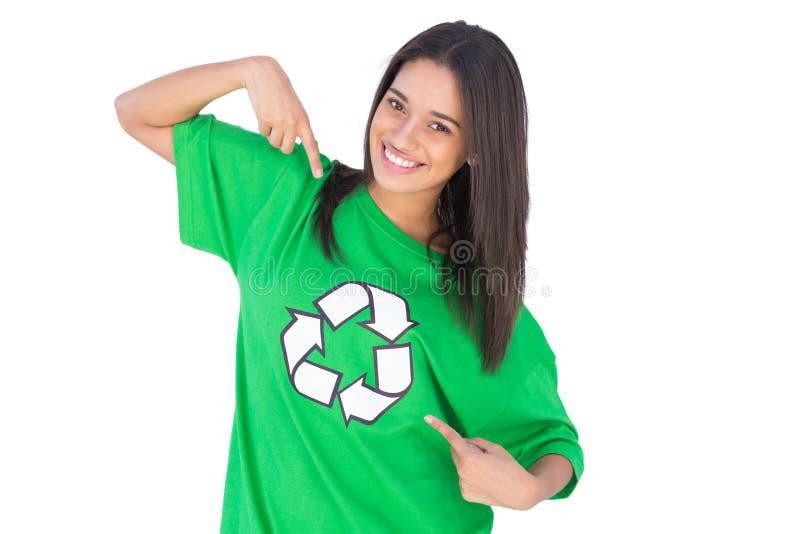 Enivromental activist pointing to the symbol on her tshirt. Enivromental activist pointing to the recycling symbol on her green tshirt stock photos