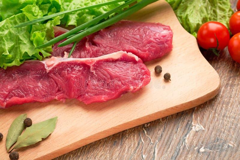 Enjeux frais, bruts, crus de veau de viande sur un hachoir en bois avec le setion photo stock