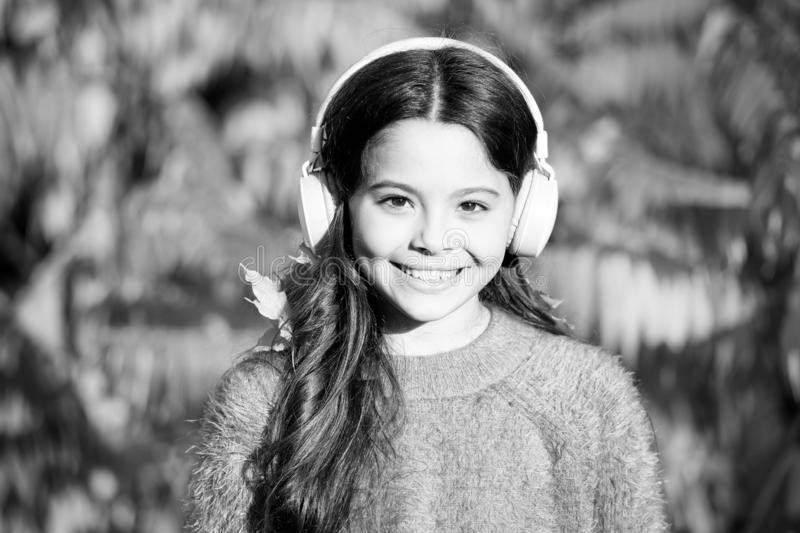 Enjoy autumn day. good day for park walk. she love nature and music. school time season. fall mood. small girl listen. Audio book. little child in headset royalty free stock images