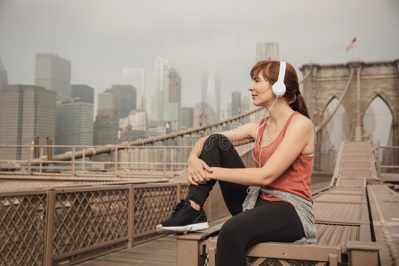 Enjoy the city life. Woman sitting on the Brooklyn bridge and looking the view royalty free stock photo