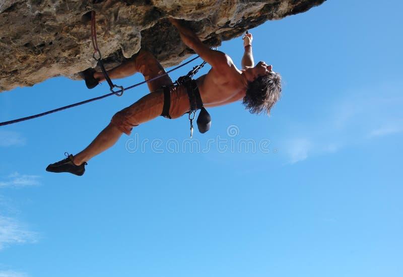 Enjoy climbing!. Adult climbing hard overhanging rock stock images