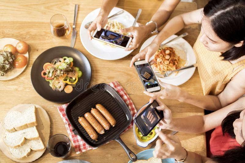 Enjoy dinner eating party with friends and taking photo by phone stock image