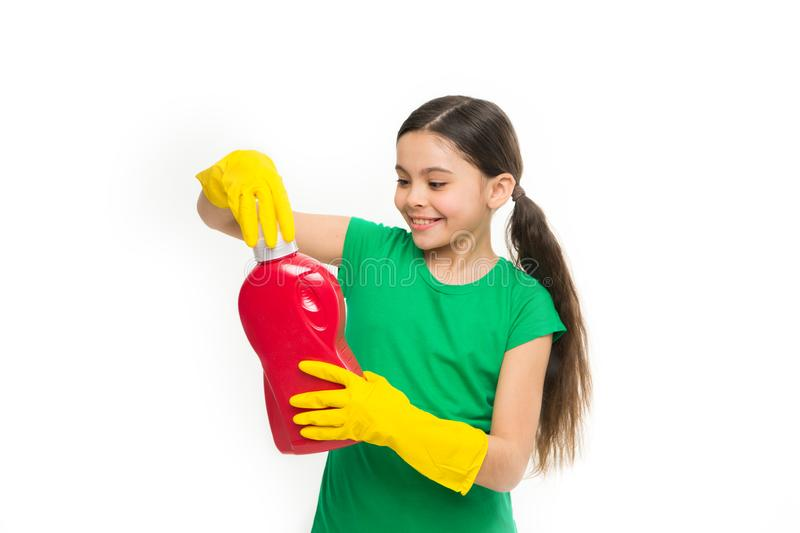 Enjoy doing her washing. Cute cleaner wearing yellow rubber gloves. Small child holding laundry detergent in hands royalty free stock photo