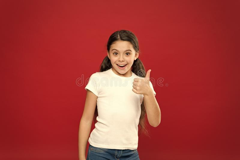 Enjoy every moment. Happy child girl with long hair on red background. Happiness and joy. Positive emotions. Child care royalty free stock images