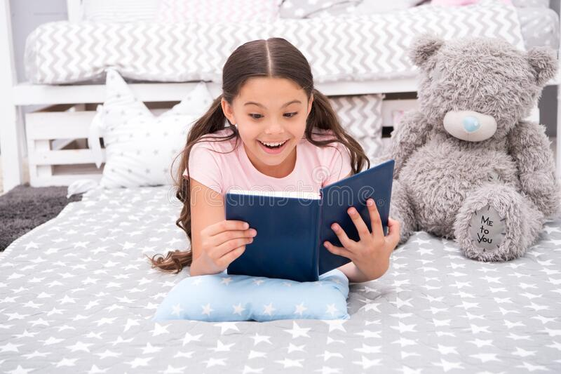 Enjoy favorite moment. Girl child lay bed with teddy bear read book. Kid prepare to go to bed. Girl kid long hair cute royalty free stock image
