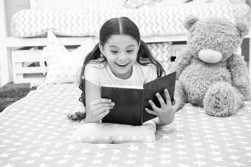 Enjoy favorite moment. Girl child lay bed with teddy bear read book. Kid prepare to go to bed. Girl kid long hair cute. Pajamas relax and read book to bear toy stock photography