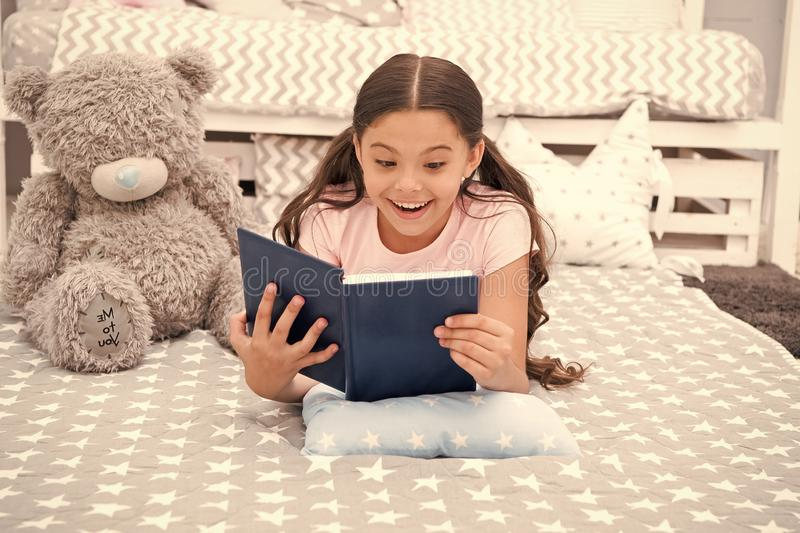 Enjoy favorite moment. Girl child lay bed with teddy bear read book. Kid prepare to go to bed. Girl kid long hair cute. Pajamas relax and read book to bear toy stock photos