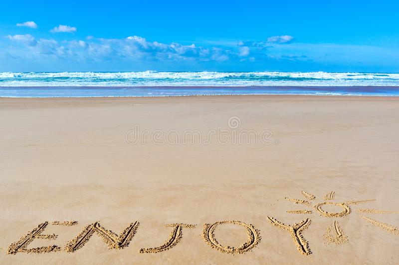 Enjoy inscription on wet beach sand under the sun drawing and se. A waves on background. Summer season holiday, vacation concept royalty free stock photos