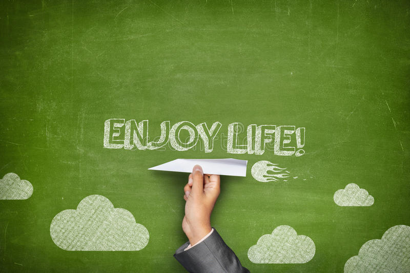 Enjoy life concept. On green blackboard with businessman hand holding paper plane stock photos