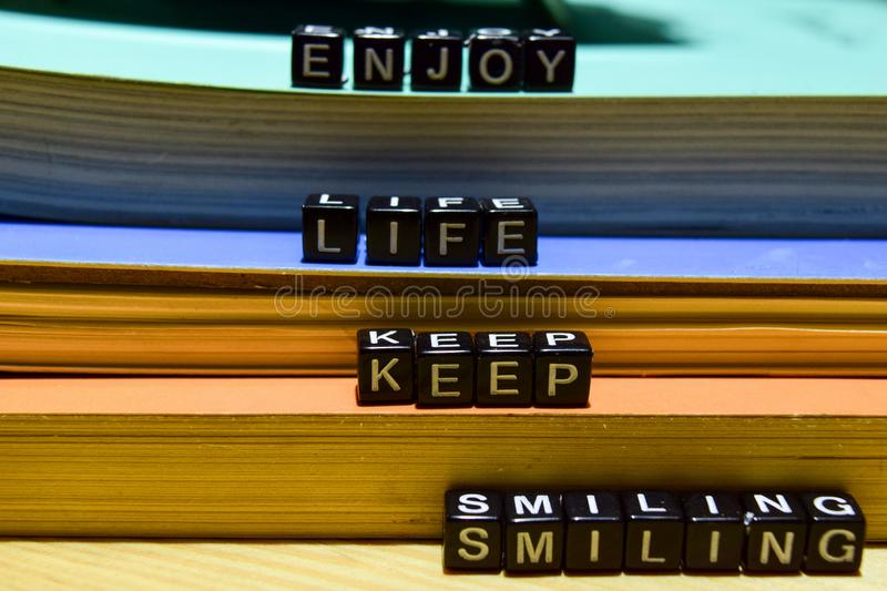 Enjoy life keep smiling written on wooden blocks. Education and business concept. On wooden background stock photos