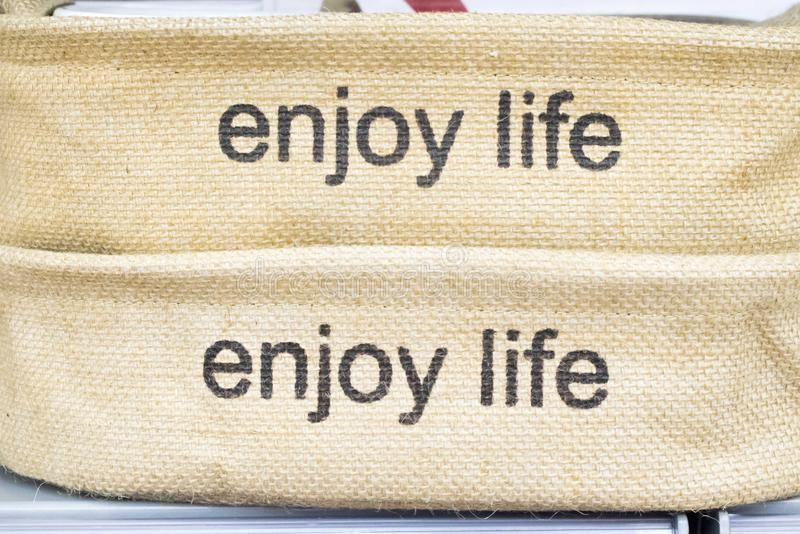 Enjoy Life- text in sack cloth letter press stock image