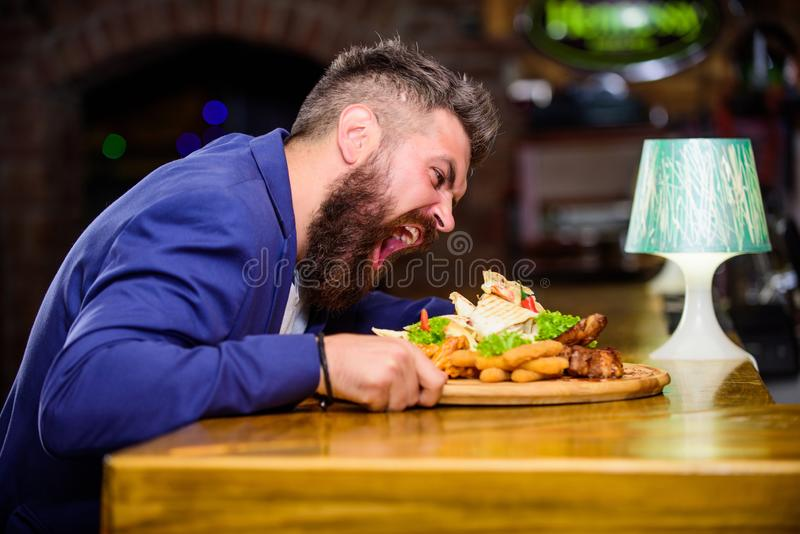 Enjoy meal. Cheat meal concept. Hipster hungry eat pub fried food. Manager formal suit sit at bar counter. Delicious. Meal. Man received meal with fried potato stock photo