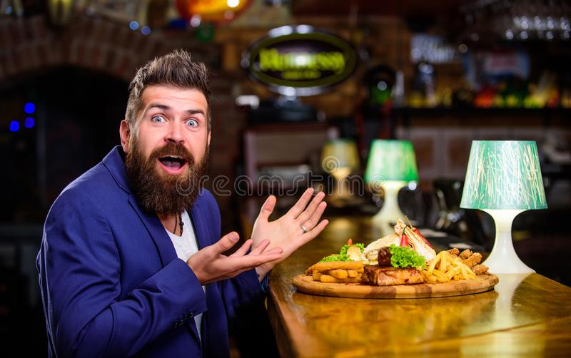 Enjoy meal. Cheat meal concept. Hipster hungry eat pub fried food. Restaurant client. Hipster formal suit sit at bar. Counter. Man received meal with fried royalty free stock photo