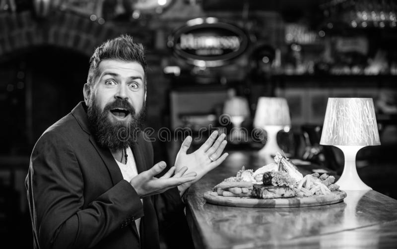 Enjoy meal. Cheat meal concept. Hipster hungry eat pub fried food. Restaurant client. Hipster formal suit sit at bar. Counter. Man received meal with fried royalty free stock photography