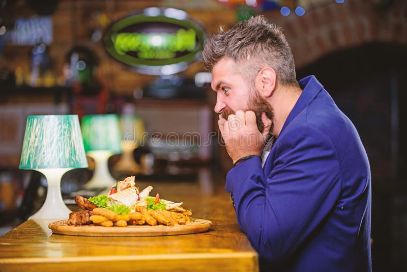 Enjoy meal. High calorie snack. Cheat meal concept. Hipster hungry eat pub fried food. Manager formal suit sit at bar. Counter. Delicious meal. Man received stock photography