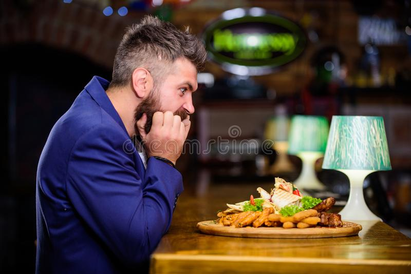 Enjoy meal. High calorie snack. Cheat meal concept. Hipster hungry eat pub fried food. Manager formal suit sit at bar. Counter. Delicious meal. Man received royalty free stock photography