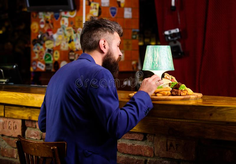 Enjoy meal. Hipster hungry eat pub fried food. Restaurant client. Hipster formal suit sit at bar counter. Man received. Meal with fried potato fish sticks meat stock photography