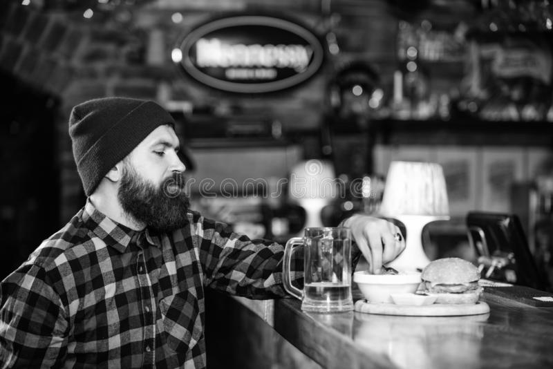 Enjoy meal in pub. High calorie snack. Brutal hipster bearded man sit at bar counter. Hipster relaxing at pub. Pub is. Relaxing place to have drink and relax stock images