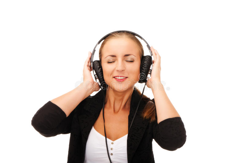 Enjoy the music. Girl with headphones and eyes closed on isolated white background royalty free stock photo