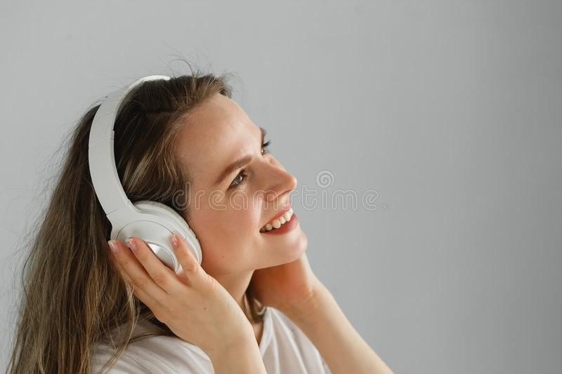 Enjoy the music. Happy young woman pleasing music in white headphones. royalty free stock photography