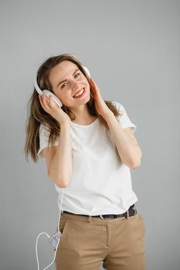 Enjoy the music. Happy young woman pleasing music in white headphones. stock photography