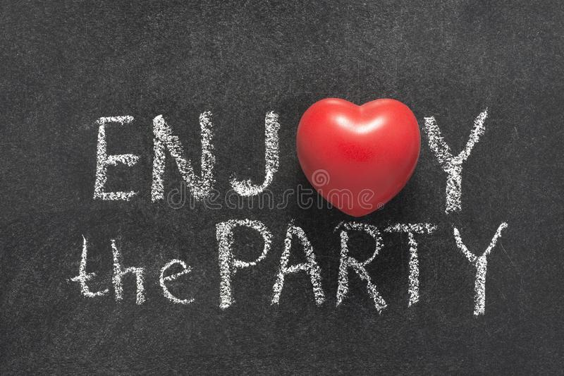 Enjoy the party. Phrase handwritten on chalkboard with heart symbol instead of O stock images
