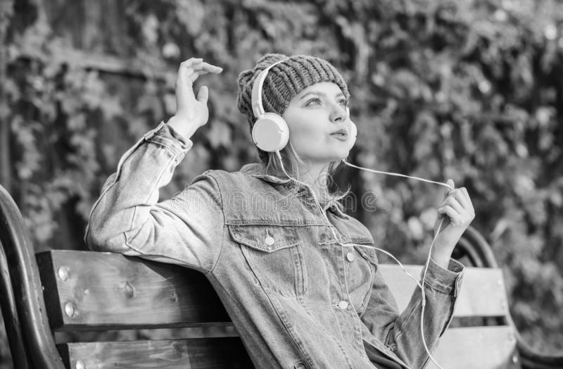 Enjoy powerful sound. Feeling awesome. Cool funky girl enjoy music in headphones outdoor. Girl listen music in park. Melody sound and mp3. Music fan concept royalty free stock photo