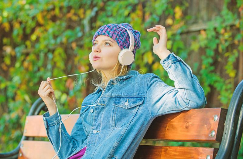 Enjoy powerful sound. Feeling awesome. Cool funky girl enjoy music in headphones outdoor. Girl listen music in park. Melody sound and mp3. Music fan concept stock photo