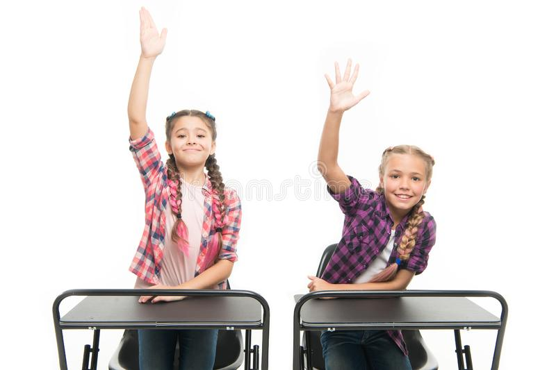 Enjoy process of studying. Little girls school friends study together. Raise hands to answer. Students classmates sit. Desk. Back to school. Private school stock photo